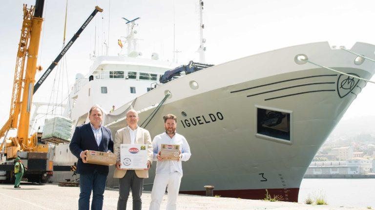 Santiago Montejo, Ramón Abeijón y Javier Otaegui frente al buque igueldo, sujetando cajas calamar patagónico